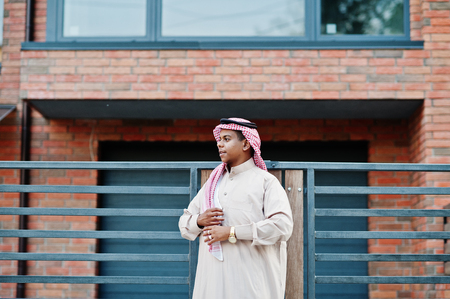Middle Eastern arab man posed on street against modern building.