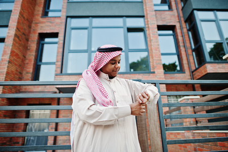 Middle Eastern arab man posed on street against modern building looking at his golden watches.