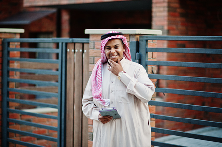 Middle Eastern arab man posed on street against modern building with tablet at hands. Stock Photo