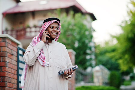 Middle Eastern arab business man posed on street against modern building with tablet and mobile phone at hands. Stock Photo