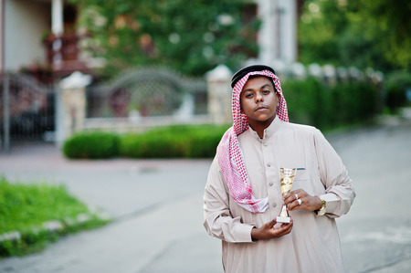 Middle Eastern arab business man posed on street with golden cup at hands. Stock Photo