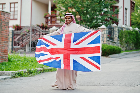 Middle Eastern arab man posed on street with Great Britain flag. England and Arabian countries concept.