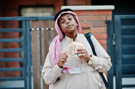 Middle Eastern arab business man posed on street against modern building with black handbag and euro moneys. Stock Photo