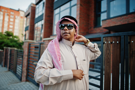 Middle Eastern arab business man posed on street against modern building with sunglasses. Stock Photo