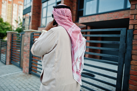 Back of Middle Eastern arab business man posed on street speaking on mobile phone.