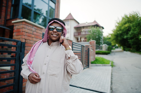 Middle Eastern arab business man posed on street against modern building with sunglasses, speaking on mobile phone.