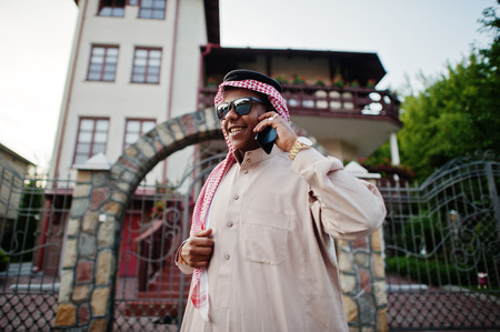 Rich Middle Eastern arab business man with sunglasses posed on street against mansion , speaking on mobile phone.