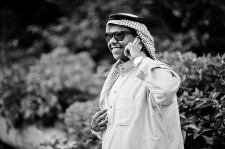 Middle Eastern arab business man posed on street with sunglasses, speaking on mobile phone.