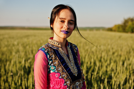 Tender indian girl in saree, with violet lips make up posed at field in sunset. Fashionable india model. Stock Photo
