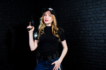 FBI female agent in cap and with gun at studio against dark brick wall.
