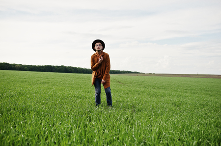 Stylish man in glasses, brown jacket and hat posed on green field.