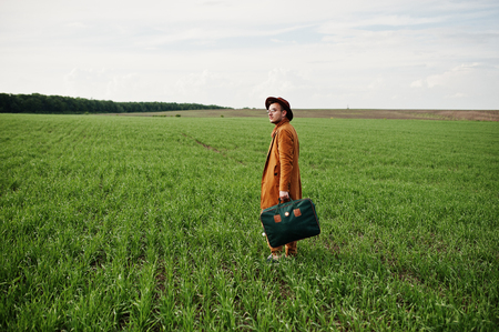 Stylish man in glasses, brown jacket and hat with bag posed on green field.