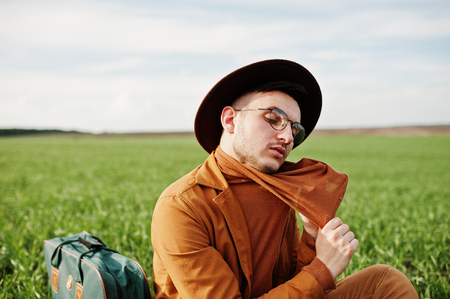 Stylish man in glasses, brown jacket and hat with bag posed on green field. Banque d'images