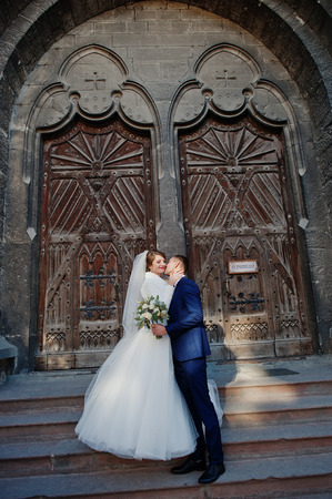 Romantic newly married couple kissing and posing by the ancient doors in an old town on their wedding day.