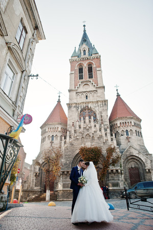 Newly married couple posing next to the old church in the town on a beautiful autumn wedding day.