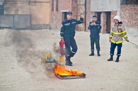 Hai, Ucrania - 10 de julio de 2018: Tutorial de cómo dar la seguridad contra incendios, extinguir el fuego. Bombero mantenga en la mano el extintor de incendios. Protección contra las llamas. Muestre las instrucciones de entrenamiento.