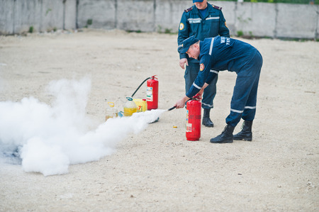 Hai, Ukraine - July 10, 2018: Tutorial how to give the fire safety, extinguish fire. Fireman hold in hand fire extinguisher. Protection from flame. Show training instructions.