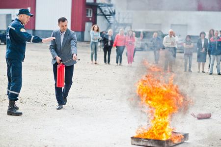 Hai, Oekraïne - 10 juli 2018: Tutorial hoe de brandveiligheid te geven, brand te blussen. Brandweerman houdt brandblusser in de hand. Bescherming tegen vlammen. Toon trainingsinstructies.
