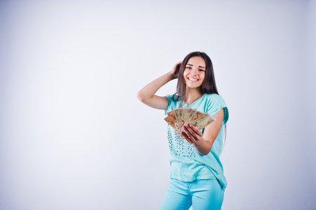 Portrait of an attractive girl in blue or turquoise t-shirt and trousers posing with a lot of money in her hand.