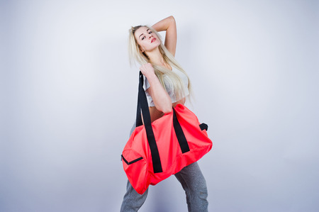 Blonde sporty girl with big sport bag posed at studio against white background.