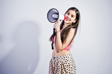 Portrait of a gorgeous young girl in swimming suit and hat talks into megaphone in studio. Banco de Imagens