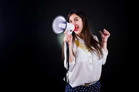 Portrait of a young woman in blue trousers and white blouse posing with megaphone in the studio. Banco de Imagens