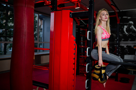 Sexy sport blonde girl punching bag. Fit woman boxing.