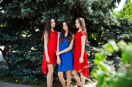 Three teenagers girl in blue and red dresses posed outdoor. Imagens