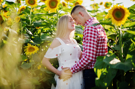 Pregnant couple in sunflowers field. Happy moments of pregnancy.