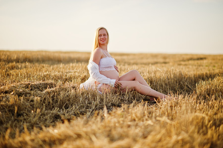 Blonde pregnant woman in wreath field at white underwear clothes on sunset. Happy moments of pregnancy. 版權商用圖片