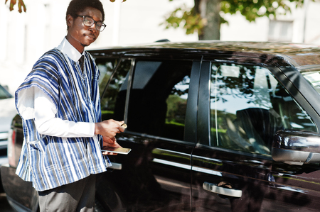 African businessman in traditional clothes and glasses open a door of his black car suv. Rich africans people.