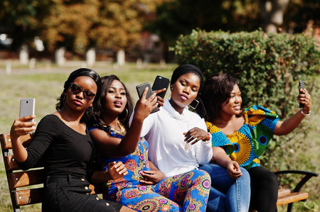 Group of four african american girls sitting on bench outdoor with mobile phones at hands and making selfie. Stock Photo