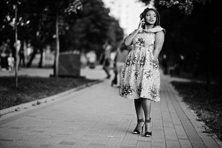 Cute small height african american girl with dreadlocks, wear at coloured yellow dress, posed at sunset, walking and speaking on cellphone. Black and white.
