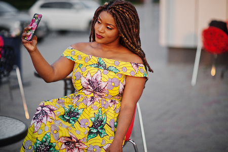 Cute small height african american girl with dreadlocks, wear at coloured yellow dress, sitting at outdoor cafe on red chair and making selfie. Standard-Bild