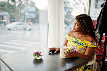 Cute small height african american girl with dreadlocks, wear at coloured yellow dress, sitting at cafe with cup of coffee and looking at window.