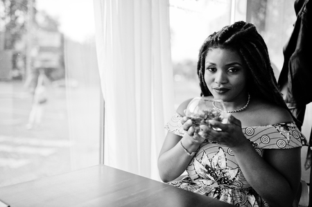 Cute small height african american girl with dreadlocks, wear at coloured yellow dress, sitting at cafe with flower at glass. Black and white. Stock Photo