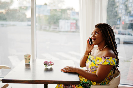 Cute small height african american girl with dreadlocks, wear at coloured yellow dress, sitting at cafe and speaking on phone.
