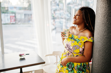 Cute small height african american girl with dreadlocks, wear at coloured yellow dress, posed at cafe with cup of coffee.