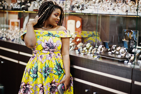 Cute small height african american girl with dreadlocks, wear at coloured yellow dress, on watches store at shopping center. Stock Photo