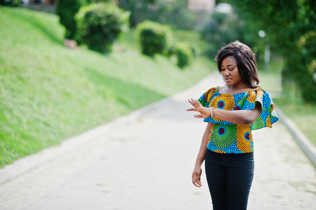 African american girl in coloured shirt and black pants posed outdoor. Fashionable black woman looking at her watches, time concept.