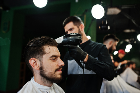 Handsome bearded man at the barbershop, barber at work, using hair dryer.