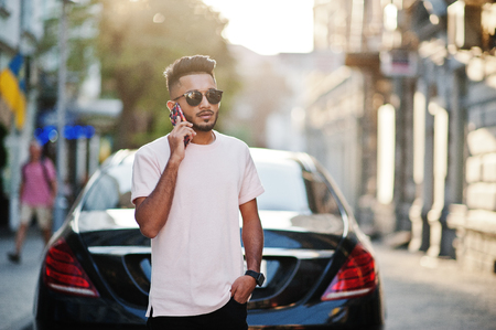 Stylish indian beard man at sunglasses and pink t-shirt against luxury car and speaking on mobile phone. India rich model posed outdoor at streets of city. 免版税图像