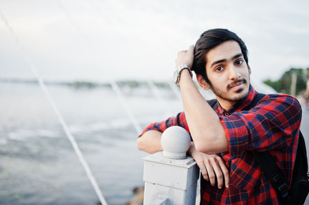 Young Indian male student in checkered shirt and jeans with backpack posed on evening city against the fountains. Stock Photo