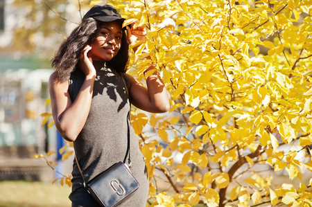 Stylish african american girl in gray tunic, crossbody bag and cap posed at sunny autumn day against yellow leaves. Africa model woman.