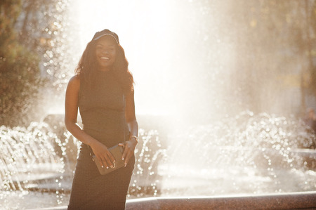 Stylish african american girl in gray tunic, crossbody bag and cap posed at sunny autumn day against fountains. Africa model woman. Stock Photo