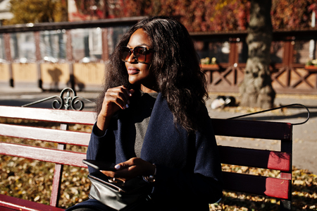 Stylish african american girl in blue coat and sunglasses posed at sunny autumn day at bench and using her mobile phone. Africa model woman with smartphone.