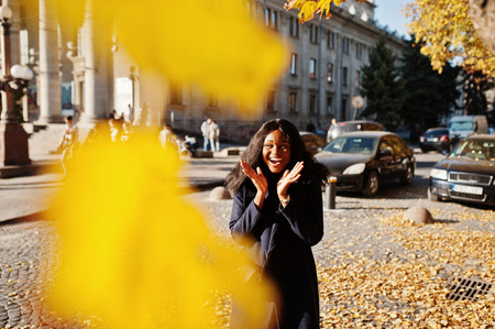 Stylish african american girl in blue coat posed at sunny autumn day. Africa model woman.