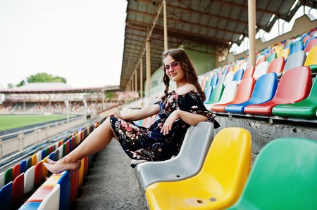Portrait of a young beutiful girl in dress and sunglasses sitting on the tribunes in stadium.