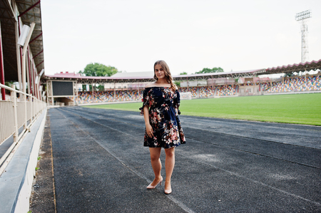Portrait of a fabulous girl in dress and high heels on the track at the stadium. Фото со стока