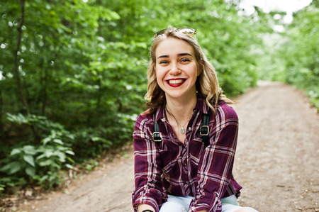 Portrait of a beautiful blond girl in tartan shirt sitting on the ground in the countryside. 写真素材